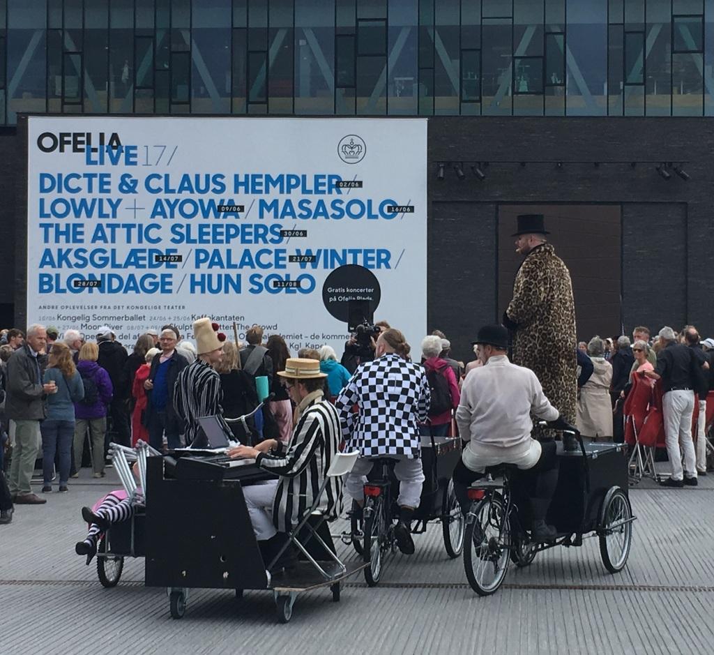 Foto fra Ofelia Plads i 2017 med operasangere og en pianist på cykel.